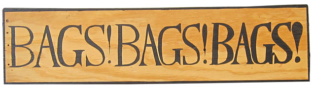 "The text ""Bags! Bags! Bags!"" painted in a serif font in black paint on a piece of light-colored wood."