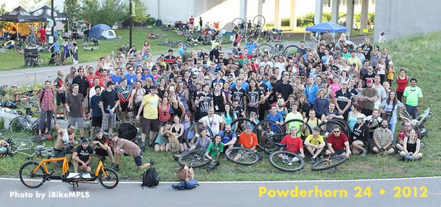 Post-race group shot from the Powderhorn 24. A crowd of participants pose with their bicycles on a hill along the Greenway in Minneapolis