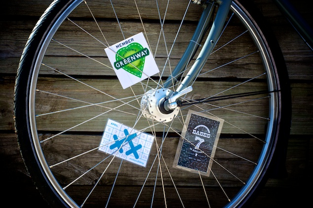 A bicycle wheel with three spoke cards, including a 30 Days of Biking spoke card